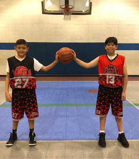 two kids each with one hand on a shared basketball standing in a gym